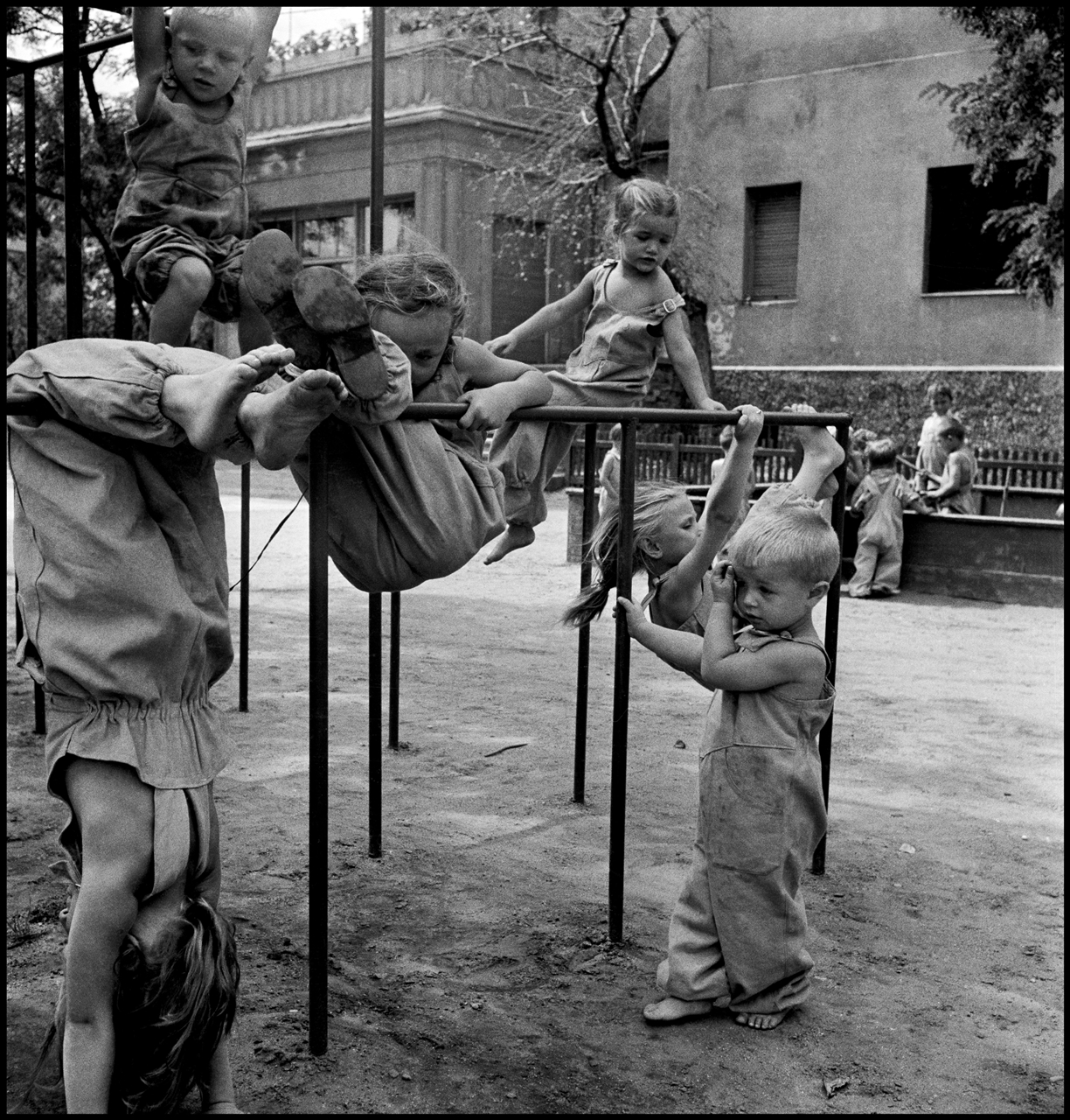 David SEYMOUR 'CHIM' | Active children of textile workers clamber over special climbing bar sin the grounds of the house of the former factory owner, now the kindergarten near Budapest, Hungary | 1948